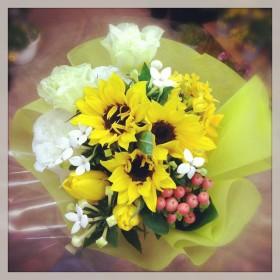 フラワーアレンジメント ひまわり、八重咲きトルコキキョウ、エビデンドラム、チューリップ、ブバルディア、ヒペリカム