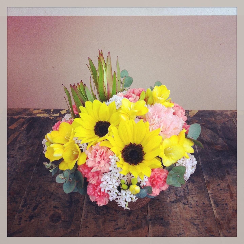 フラワーアレンジメント使用花材 ひまわり、大輪カーネーション、フリージア、スプレーカーネーション、サクラコマチ、リューカデンドロン、ユーカリ