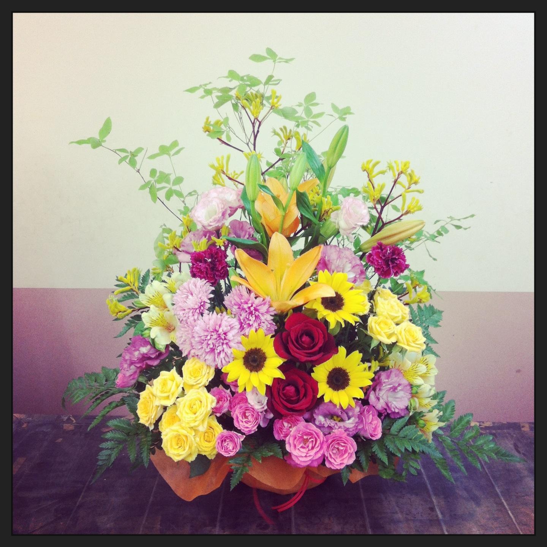 フラワーアレンジメント使用花材 すかしゆり、大輪バラ、ひまわり、大輪カーネーション、アスター、八重咲きトルコキキョウ、スプレーバラ、アルストロメリア、カンガルーポー、アブラドウダンツツジ、レザーファン