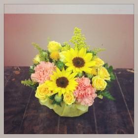 フラワーアレンジメント使用花材 ひまわり、大輪カーネーション、スプレーバラ、紅花、ソリダコ、レザーファン