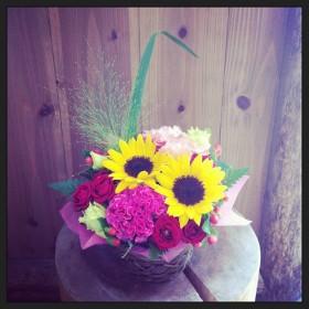 フラワーアレンジメントヒマワリ、八重咲きトルコキキョウ、ケイトウ、スプレーバラ、ヒペリカム、オオニソガラム、レザーファン