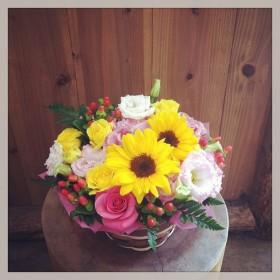 フラワーアレンジメント ヒマワリ、八重咲きトルコキキョウ、ヒペリカム、スプレーバラ、レザーファン